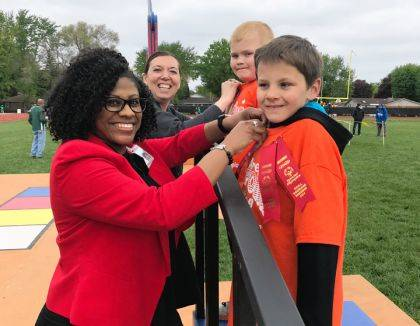 At the 2019 Special Olympics Track & Field Day, Terri Flood and Lauren Henry, of the Wayne HealthCare Foundation, presented ribbons to Brayden Fritz and Wyatt Stewart.