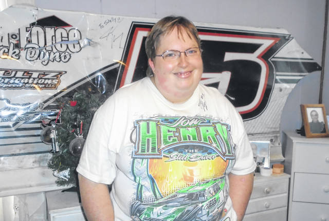 Shelly Hoffman , a fan of John Henry, a late model race car driver at Eldora Speedway, is shown in the bedroom of her home wearing one of his T-shirts and showing off the panel of one of his cars he gave to her. The young woman is ready for a healthy new year in 2020.
