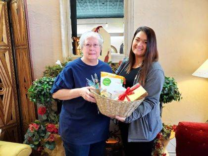 Kendra Brewer of Tribute Funeral Homes (right) presented Betty Henry of Arcanum (left) with the February Cancer Basket at Montage Café.