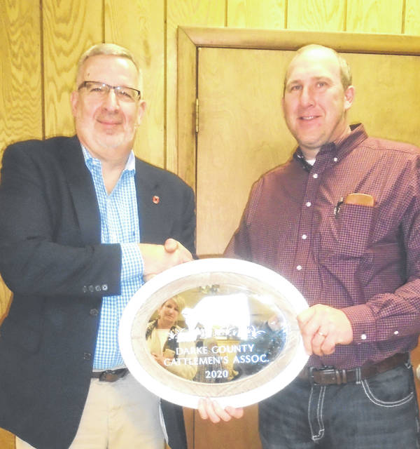 Darke County Extension Educator Sam Custer, left, is congratulated by a Darke County Cattlemen's Associaton Director, Brian Winner, for rceiving the director's award presented each year at the DCCA's annual banquet.