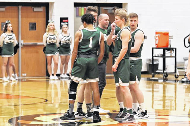 Greenville coach Kyle Joseph and the starting five meet a midcourt before the opeing tip at Versailles