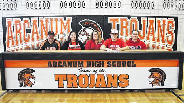 Arcanum Trojans Grant Delk signs to pitch for the Sinclair baseball program. (L-R) Randy Baker (Arcanum baseball coach), Paige Christ (sister), Nikki Delk (mother), Delk and Brad Delk (father).