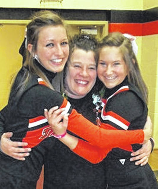 Kami Shinn Phlipot gets hugs here from two of her former cheerleaders: Sarah Amspaugh (now Bey), on the left, and Mackenzie Miller (now Stewart). The photo was taken in 2014.