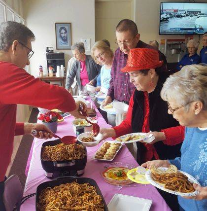 At left, Sam Casalano, CEO of the YMCA of Darke County, serves up his famous spaghetti for the fifth year in his annual tradition at the SilverSneakers luncheon at the Greenville facility.
