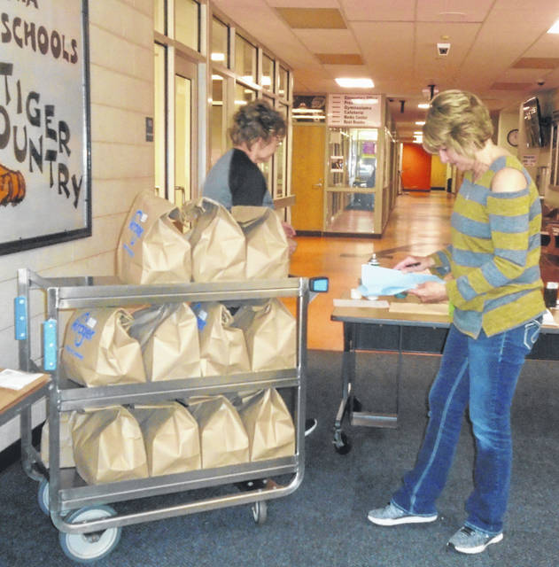 Pat Kaiser, left, and Paula Moody check their lists inside the Ansonia School for the school lunches they made to make sure children get their weekly meal.