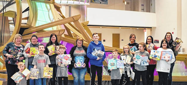 Shown with the books they purchased to take to Dayton Children's Hospital were, front row from left to right, Alex Clopp (a future Junior Granger), Moxon Gilpin. Joey Clopp, Calen Clopp, Dessie Wolf, Haddie Gilpin and Madelyn Dillon; and back row, Kelly Wills, Susan Gunckle, Holly Clopp, Lynne Hinshaw, Jaden Wolf, Sarah Loxley and Ashley Gilpin.