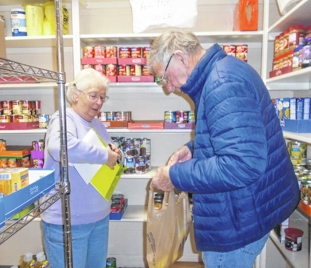Judy and Bill Collins get a bag of food ready for distribution at the Ansonia Community Food Pantry. Food is distributed on Monday mornings and Thursday evenings by appointment only.