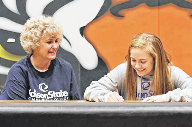 Versailles senior Caitlin McEldowney (R) signs to play basketball for Edison State while her mother, Holly McEldowney (L) looks on.