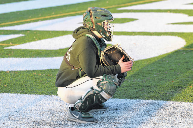 Greenville sophomore Seth Delk takes his place behind the plate for the Greenville varsity baseball team early season practice.