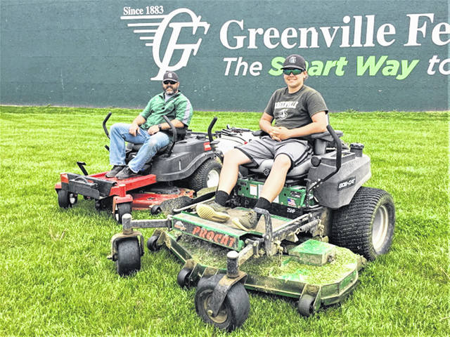 Father and son, Adam and Jackson Eberwein take time to mow the baseball fields at Greenville's Sater Heights Ballpark.