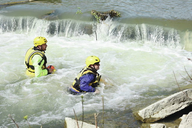 Luke Gronneberg | Sidney Daily News Rescue workers probe the base of the dam next to Stolle Bridge on Saturday, May 2, as the search for a man who has been missing since April 27.
