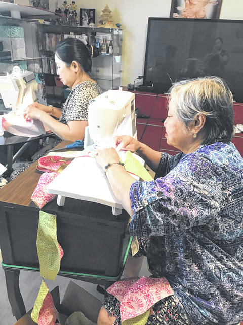 Working on sewing masks in their home during the pandemic are sisters Van, on the left, and Thuy Nguyen. The women are daughters of Lam Van, who also helps as do their children. They have found something to do in the stay-at-home order that was put in place recently.