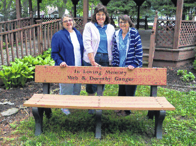 Provided photo Anna Lee Dickerson, Judi Pence, and Patty Foreman stand behind the bench they purchased and placed on the Darke County Fairgrounds in honor of their parents Web and Dorothy Ganger.