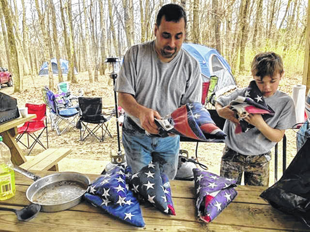 Greg Zechar, manager of Zechar Bailey Funeral Home in Greenville, teaches area Boy Scouts the proper handling, folding, and decommissioning of a flag. The funeral homes hold four decommission ceremonies each year.