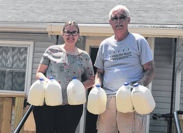 Versailles FFA Historian Laura Wuebker is shown delivering milk to Versailles Council of Churches as part of the ARCOP grant. Laura is shown with Dan Brown representing the Council of Churches. Versailles FFA plans to continue to support this program throughout the summer and fall.