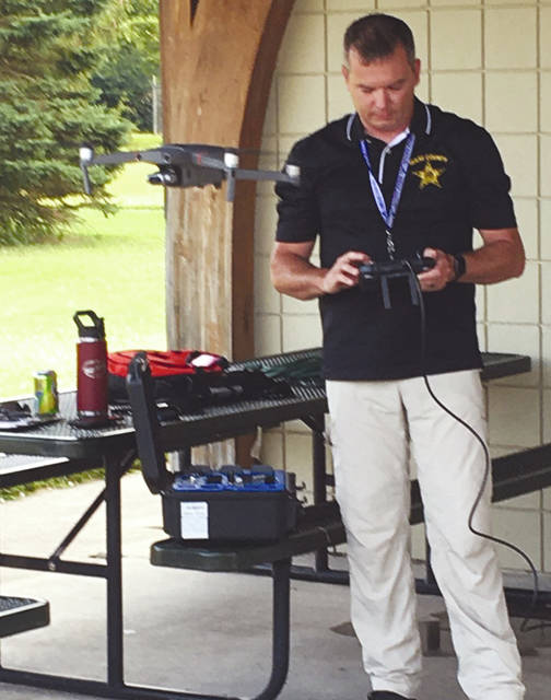 Provided photo Miami County Sheriff's Office Deputy Rich Mann with the drone hovering in front of him.