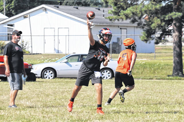 Arcanum assistant coach TJ Powers watches a pass play by the Trojans high school team.