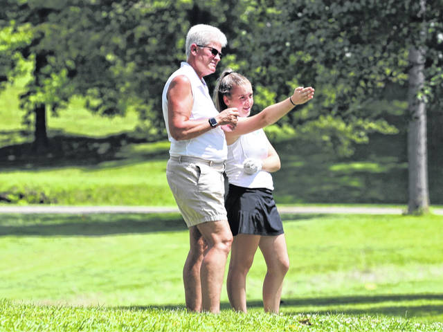Greenville Lady Wave golf coach, Tracy Hanes takes time to listen to one of her players.