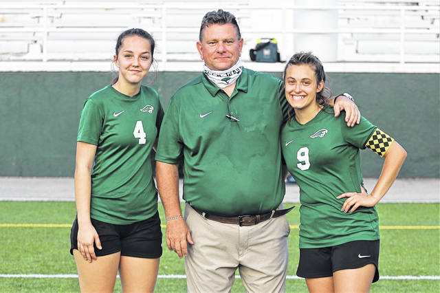 Greenville honors two Lady Wave senior soccer players. (L-R) Aeris Raffel, Coach Dave Ernst and Kendra Arnold.