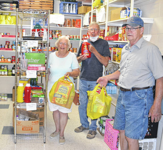 Volunteers at the Ansonia Food Pantry organize items purchased with a grant from the COVID-19 Relief Fund at the Darke County Foundation. Pictured (l to r): Judy Collins, Bill Collins, and Doug Shellhaas, all of Ansonia.