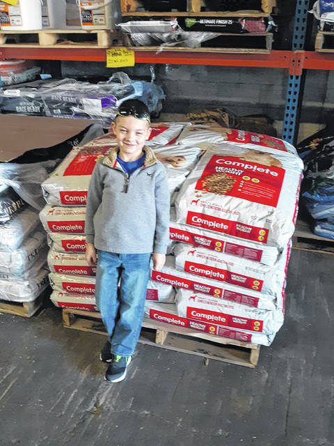 New Madison boy, Beckett Bolton stands in front of a 'skid' of dog food to be donated to Darke County Animal Shelter.