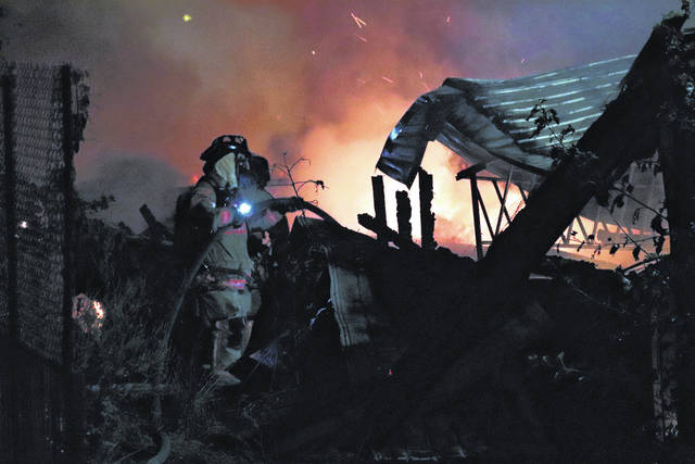 A fire fighter extinguishes embers at a barn fire in Ansonia Friday evening. The entire structure and its contents were lost.