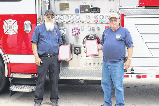 Long-time fire volunteers Mervin Hilty (left) and James Rush (right) were lauded by Liberty Township Fire Department, with the department's new fire engine dedicated in their honor.