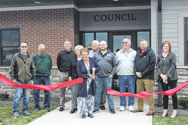 Arcanum Mayor Bonnie Millard, alongside a number of village council members, cuts the ribbon for the official opening of the town's new government building located at 309 S. Albright Street.