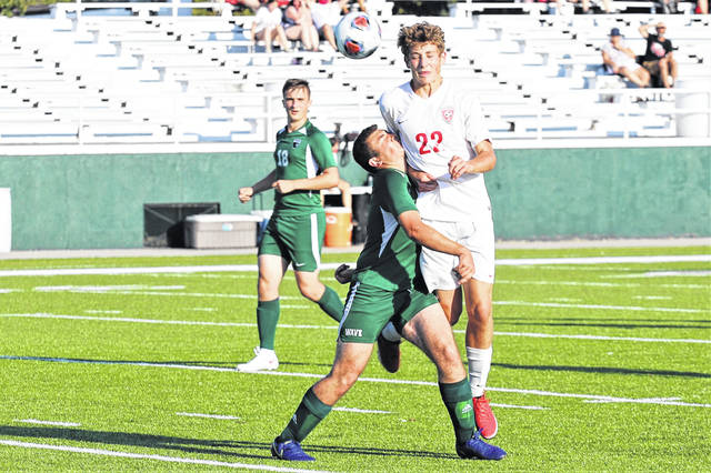 Jordan Werner looks on as Ben Davidson battles for control in Greenville and Tippecanoe soccer matchup.