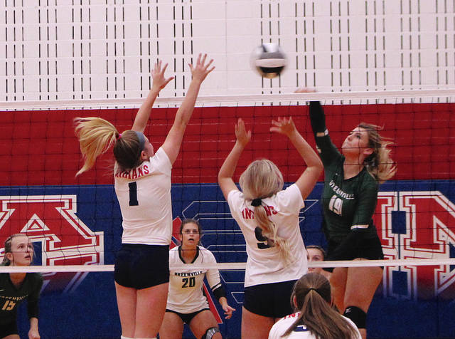 Rob Kiser|Daily Advocate Greenville's Hunter Class hits the ball as Piqua's Cara Reed (1) and Reygan Weaver (9) attempt to block it Tuesday.