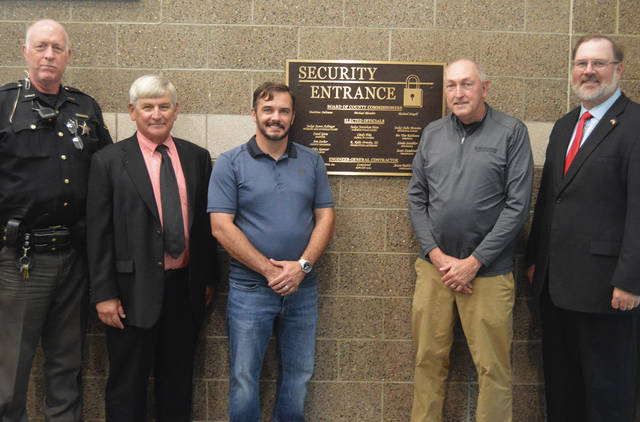 From left to right, Deputy Ron Beisner, Darke County Commissioner Mike Rhoades, Darren Reeves and Mike Henderson of Mote & Associates and Darke County Commissioner Matt Aultman stand in front of the new Security Entrance sign at the Darke County Courthouse.
