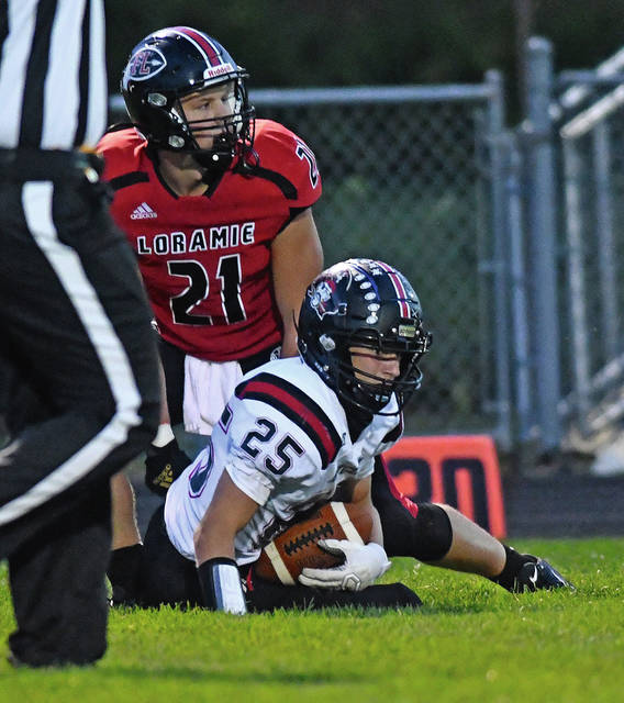 Covington's David Robinson recovers a fumbled punt as Fort Loramie's Nate Meyer looks on Thursday night.