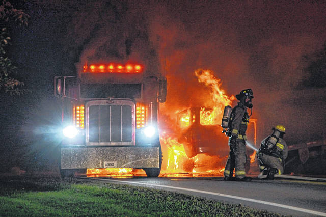 Fire fighters battle flames following a collision Tuesday evening between a semi-tractor trailer and an SUV at the 2800 block of State Route 502. No life-threatening injuries were reported.