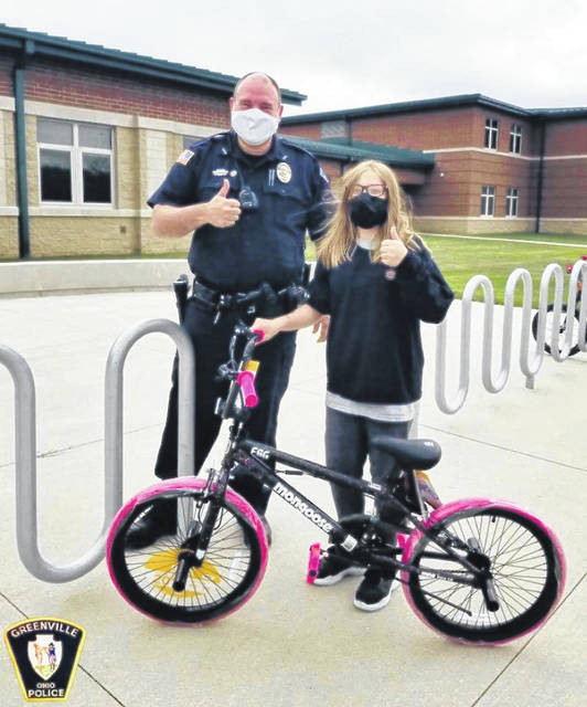 Greenville School Resource Officer Ryan Borowske presents a new bicycle to a Greenville Middle School student, replacing a bike which was stolen.