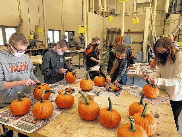 Owen DeMange, Jeramiah Wagner, Emma Middendorf, and Colleen Palaisa are shown decorating pumpkins in the ag shop that were delivered to the Versailles Health Care Center.