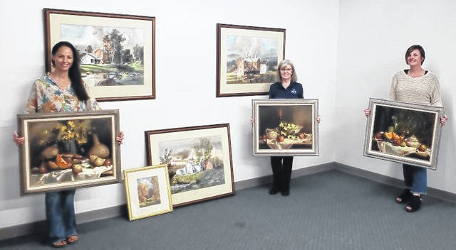 Vickie Wessling of Park National Bank with Andrea Jordan, DCCA Executive Director and Tamera McNulty, Anna Bier Gallery Director with the Bob Brubaker Collection of paintings donated to Darke County Center for the Arts.