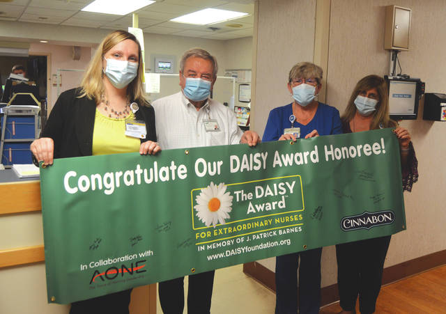 Wayne HealthCare RN and Charge Nurse Deb Osborne was presented with the DAISY Award Wednesday. Holding the banner she was presented with (from left) are VP of Patient Care Services and Chief Nursing Officer Kim Freeman, CEO Wayne Deschambeau, Osborne and Sharlyn Hickey.