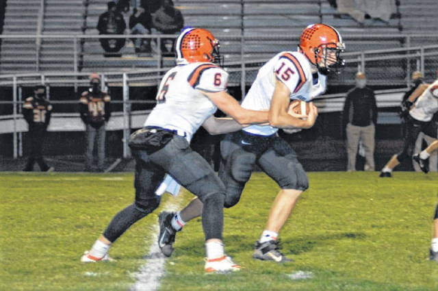 Carson Bey hands off to Landon Henry in the Versailles Tigers road game at New Bremen.