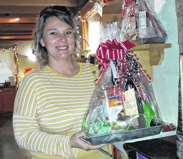 Events Coordinator Carlena Sneed highlights one of the many baskets of 'good cheer' offered at Saturday's Kristkindel Market and throughout the holiday season at The Winery at Versailles, 6572 St. Rt. 47, in Versailles.