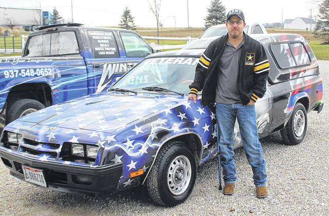 Borem poses alongside the vehicle, custom detailed with an American flag, dog tags, an eagle, and a mark symbolizing his veteran status.