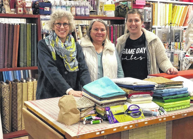 "Ohio Arts Council Residency Artist, Kate Gorman (left), stands with Diane Cooper Martin, owner of the Red Barn Quiltery, and Mississinawa Valley Art Instructor, Ashley Austerman. Martin's shop donated fabrics and supplies to support the ""Art in the Darke"" quilt project."