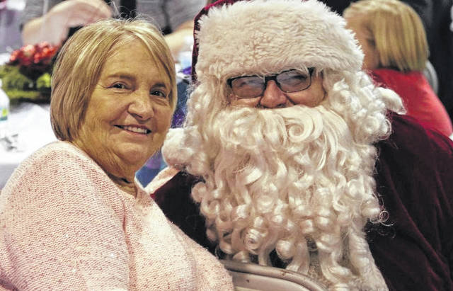Barbara Fee, founder of the Community Christmas Dinner, shown smiling with Santa Claus in 2018. The 39th Annual Community Christmas Dinner, hosted by the Radiant Lighthouse, will take place from 11 a.m. to 1 p.m. on Dec. 25th, with a drive-thru for meal pickup and Christmas toys and gifts. The event is free and open to the public.