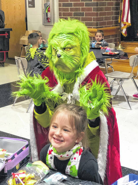 """Not even an appearance by the Grinch, himself, can stop student Emery Linebaugh (pictured) from giggling at lunchtime while visiting with Santa on """"Grinch Day"""" at Mississinawa Elementary School in Union City."""