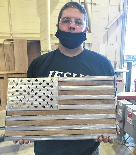 Austin Nerderman is shown with the flag that he welded as part of the Mechanical Principles.