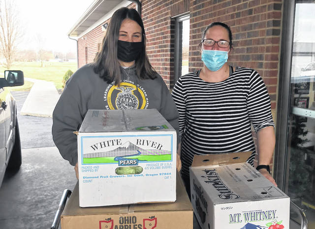 On Dec. 14, the Versailles FFA donated a box of apples, a box of pears, and a half box of clementines to Versailles Kinder Korner and Brilliant Beginnings. Shown is Versailles FFA member Cayla Batten, with Brilliant Beginnings staff member DJ Macleodas, as a part of the Versailles FFA recent fruit donation.