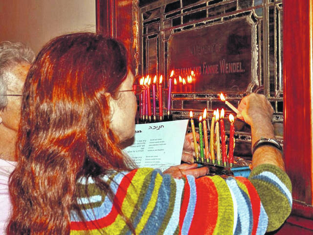 Members of the Congregation of Anshe Emeth gather and light candles on the menorah to celebrate Hanukkah, known as the Festival of Lights, which lasts eight days and nights.