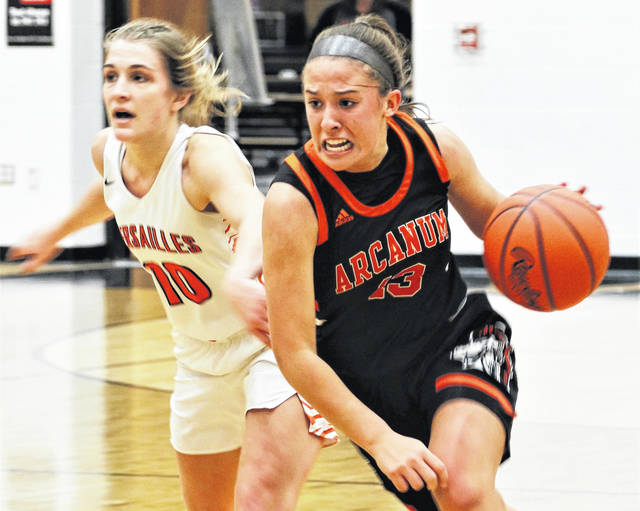Abby Stammen (10) defends as Arcanum's Madelyn Fearon (13) brings the ball upcourt in the Lady Trojans non-conference win over Versailles.