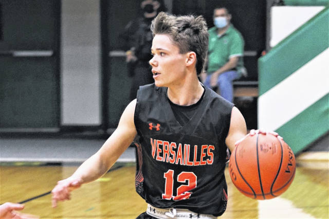 Troy Jones brings the ball upcourt for Versailles in the Tigers season opener at Celina.