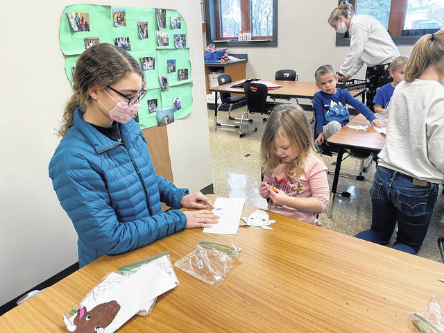 Cora Trissell is shown helping a Versailles Preschool student make goat puppets following watching the Farm Day goat video.