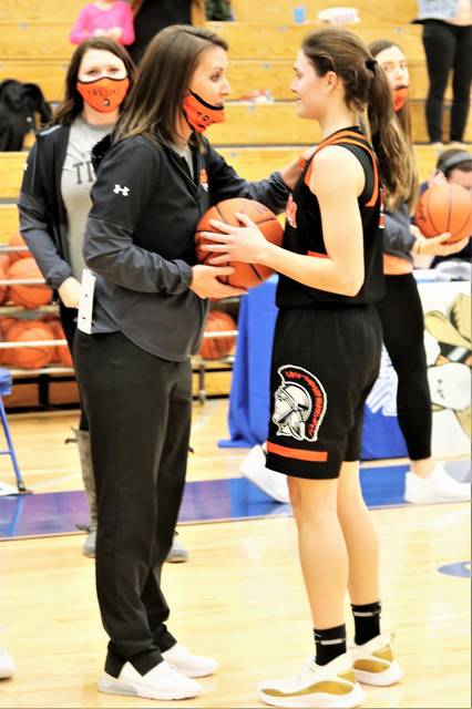 Arcanum coach, Abbie Moore presents Hailey Unger the game ball following her 1,000th career Lady Trojans varsity girls basketball point.